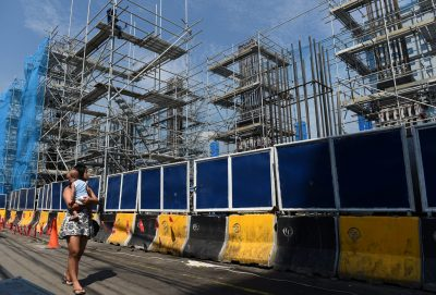 A woman carrying a baby passes though a construction of the Metro Rail Transit on Commonwealth Avenue in Quezon City, metro Manila, 23 May 2018 (Photo: Reuters/Dondi Tawatao).