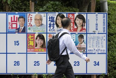 A man walks past a poster board erected in Tokyo with candidates' posters for the July 21 Upper House election (Photo: Rodrigo Reyes Marin/AFLO/Reuters).