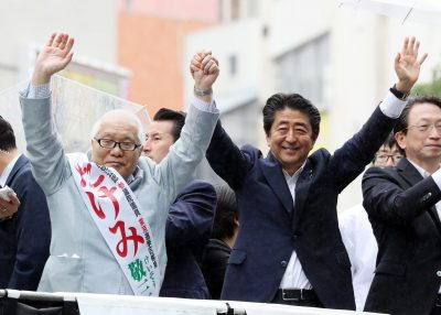 Japanese Prime Minister and leader of the ruling Liberal Democratic Party (LDP) Shinzo Abe raises his hands with his party candidate Keizo Takemi (L) at a campaign for the July 21 Upper House election in Tokyo on Sunday 7, July, 2019. (REUTERS/Yoshio Tsunoda)
