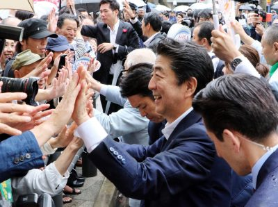 Japanese Prime Minister and leader of the ruling Liberal Democratic Party (LDP) Shinzo Abe shakes hands with his supporters after he delivered a campaign speech for his party candidate Keizo Takemi for the 21 July Upper House election in Tokyo on Sunday, 7 July 2019. (Photo: Yoshio Tsunoda/AFLO).