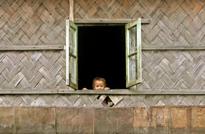 An Indian boy looks out from a window in Khonoma village, on the outskirts of Kohima, the capital of northeastern Indian state of Nagaland, 12 August 2005. (Photo: Reuters/Adnan Abidi).