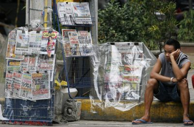 A newspaper vendor waits for customers along a street in Manila (Photo: Reuters/Romeo Ranoco).