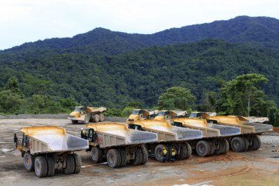 Workers inspect a fleet of earth-moving trucks, Solomon Islands (Photo: Reuters/James Regan).
