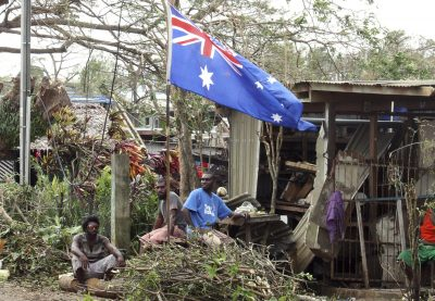 """Local residents sit outside their damaged homes surrounded by debris on a street after Cyclone Pam hit Port Vila, the capital city of the Pacific island nation of Vanuatu 15 March 2015. The first aid teams to reach Vanuatu on Sunday encountered widespread devastation and authorities declared a state of emergency after the """"monster"""" cyclone tore through the vulnerable Pacific island nation. With winds of more than 300 kph (185 mph), Cyclone Pam razed homes, smashed boats and washed away roads and bridges as it struck late on Friday and into Saturday. Aid workers described the situation as catastrophic. The count of confirmed deaths was at 10 with 20 people injured. But those numbers were almost certain to rise as rescuers reached the low-lying archipelago's outlying islands. (Photo: Reuters/Kris Paras)"""