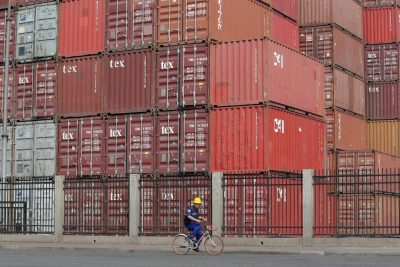 A worker cycles past containers outside a logistics center near Tianjin Port, China, 16 May 2019 (Photo: Reuters/Jason Lee).