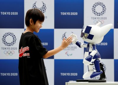 Tokyo 2020 mascot robot Miraitowa, which will be used to support the Tokyo 2020 Olympic and Paralympic Games, exchanges high-five with a boy during the robot unveiling event to celebrate the first anniversary of the mascot debut at Tokyo Stadium in Tokyo, Japan. 22 July 2019, (Photo: Reuters/Issei Kato).