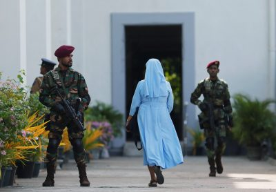 A nun arrives as a Sri Lanka's commando soldier stands guard in front of the main entrance to St. Lucia Cathedral as survivors and families of victims of Sri Lanka's Easter Sunday bombing arrive for a special mass for those who lost their lives, in Colombo, Sri Lanka, 11 May 2019 (Photo:Reuters/Dinuka Liyanawatte/File Photo).
