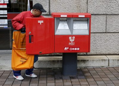 A worker of Japan Post Co, which has faced controversy for its different treatment of workers, collects postal items from a post box outside a post office in Tokyo, Japan, 2 November 2015 (Photo: Reuters/Toru Hanai).