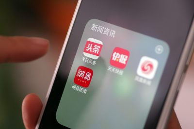 A Chinese mobile phone user looks at the icons of the mobile apps of (from top left) Toutiao, Tiantian Kuaibao, Phoenix News and NetEase News on a smartphone in Ji'nan city, Shandong, China, 9 April 2018 (Photo: Reuters).