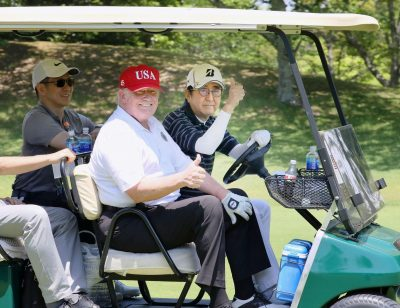 US President Donald Trump sits on a cart as Japanese Prime Minister Shinzo Abe drives the cart as they play golf at Mobara Country Club in Mobara, Chiba prefecture, Japan, 26 May 2019 (Photo: Reuters/Kyodo/Japan's Cabinet Public Relations).