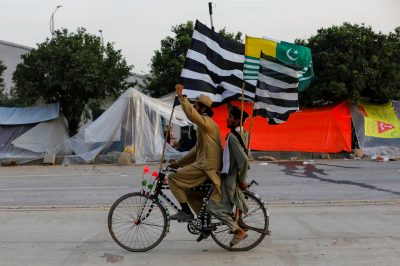 Supporters of religious and political party Jamiat Ulema-i-Islam-Fazal (JUI-F) chant slogans as they ride on a bike with flags of the party and Azad Kashmir, during the so called Azadi March (Freedom March), called by the opposition to protest against the government of Prime Minister Imran Khan in Islamabad, Pakistan 11 November 2019. (Photo:Reuters/Akhtar Soomro).