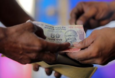 A customer hands a 50-Indian rupee note to an attendant at a fuel station in Ahmedabad, India, 5 October 2018, (Photo: Reuters/Amit Dave).