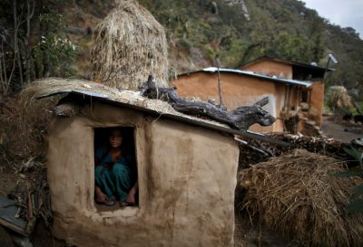 Uttara Saud, 14, sits inside a Chaupadi shed in the hills of Legudsen village in Achham District in western Nepal, 16 February 2014 (Photo: Reuters/Navesh Chitrakar/File Photo).