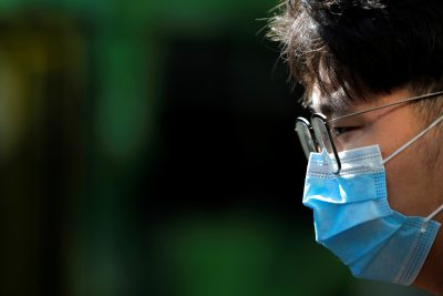 A person wearing a face mask stands on Swanston Street after cases of the coronavirus were confirmed in Melbourne, Victoria, Australia, 29 January, 2020 (Photo: Reuters/Kelly).