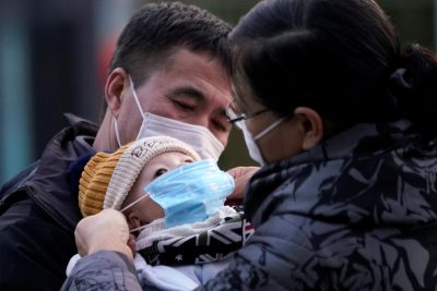 Passengers help a baby wear a mask at the Shanghai railway station in China, 9 February 2020 (Photo: Reuters/Aly Song).