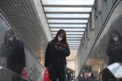 A woman wearing a face mask looks at her phone while riding an escalator, following an outbreak of the novel coronavirus in the country, in Beijing, China 23 February, 2020 (Reuters/Stringer).