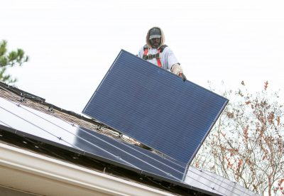Terell Odom, of Compass Solar Energy, moves a solar panel into place on a house in Milton, 11 Dec 2019 (Photo: Reuters).