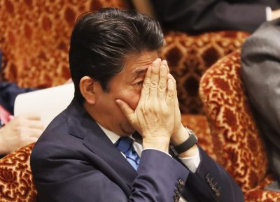 Japanese Prime Minister Shinzo Abe covers his face with his hands as he lisyens to a question by an opposition lawmaker at the National Diet in Tokyo, 3 March 2020 (Photo: Reuters/Yoshio Tsunoda/AFLO).