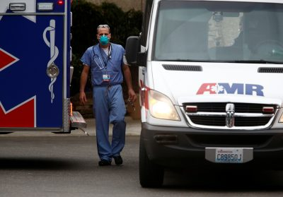 A doctor walks near an ambulance at the Life Care Center of Kirkland, a long-term care facility linked to several confirmed coronavirus cases, in Kirkland, Washington, United States, 5 March 2020 (Photo: Reuters/Lindsey Wasson).