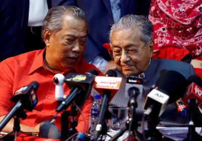 Former Malaysian Prime Minister Mahathir Mohamad listening to current Prime Minister Muhyiddin Yassin during a news conference, 5 April 2018 (Photos: Reuters/Lai Seng Sin).