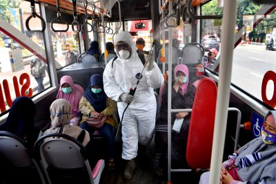A worker sprays disinfectant in the bus, to prevent the spread of coronavirus disease (COVID-19) in Surabaya, East Java Province, Indonesia, 22 March 2020 (Photo: Antara Foto/Zabur Karuru via REUTERS).
