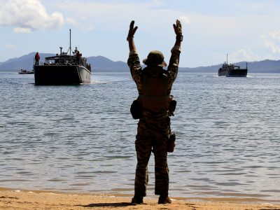 A Filipino soldier displays a hand signal to the landing ships before it docks at Motiong beach, as part of the Humanitarian Assistance and Disaster Response scenario during the Philippines and United States annual Balikatan (Shoulder-to-Shoulder) exercises in Casiguran, Philippines, 15 May 2017 (Photo: REUTERS/Romeo Ranoco).