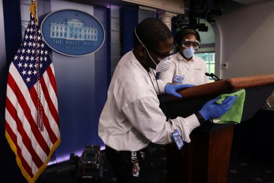Workers disinfect the podium before the start of US President Donald Trump's daily coronavirus disease (COVID-19) outbreak task force briefing at the White House in Washington DC, 9 April 2020 (Photo: REUTERS/Jonathan Ernst).