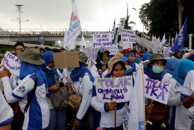 Women laborers carry placards stating 'Against Omnibus Law and Foreign Workers' as they participate in a protest outside Indonesia's parliament building in Jakarta, Indonesia, 20 January 2020 (Photo: Reuters/Willy Kurniawan).