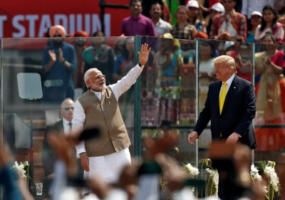 """India's Prime Minister Narendra Modi waves next to U.S. President Donald Trump as they attend the """"Namaste Trump"""" event at Sardar Patel Gujarat Stadium, in Ahmedabad, India, 24 February 2020 (Reuters/Francis Mascarenhas)."""
