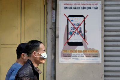 Men wear protective masks as they walk past a poster warning against the spread of 'fake news' online on the new coronavirus in Hanoi, Vietnam, 14 April 2020 (Photo: Reuters/Kham).