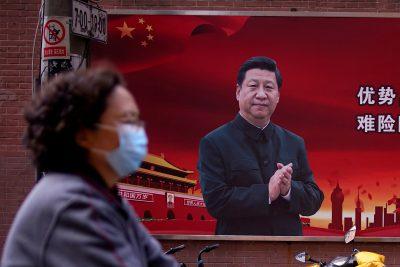 Une femme portant un masque de protection passe devant un portrait du président chinois Xi Jinping dans une rue alors que le pays est touché par une épidémie de coronavirus, à Shanghai, Chine, le 12 mars 2020 (Photo: Reuters / Aly Song / File Photo).