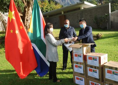 The Consulate General of the People's Republic of China, Lin Jing (right) delivered food and medical supplies to Vice President of Parliament Solomon Lechesa Tsenoli (center) in Cape Town, South Africa 13 May 2020 (Courtney Africa/ ANA/Latin America News Agency via Reuters).