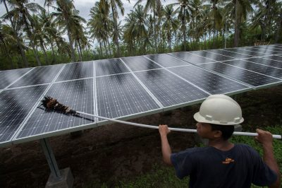 An employee of PT Perusahaan Listrik Negara (PLN) cleans the surface of solar panels at a solar power generation plant in Gili Meno island, in this 9 December 2014 photo taken by Antara Foto (Reuters/Antara Foto/Widodo S. Jusuf.).