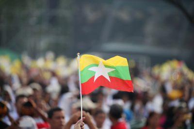 Person waving a Myanmar flag at Kyite Ka San Football Stadium in Yangon, Myanmar, 29 November 2017 (Photo: Reuters/Soe Zeya Tun).