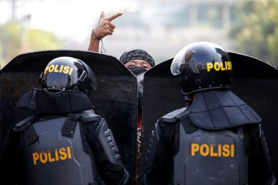 A protester gestures as mobile brigade (Brimob) police officers stand guard at a barricade during a protest in Jakarta, Indonesia, 22 May 2019 (Photo: Reuters/Willy Kurniawan).