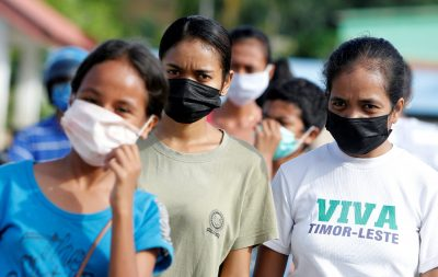 Women wearing protective masks look on as they walk on a street after the government announced new cases of coronavirus disease (COVID-19), in Dili, East Timor, 16 April, 2020. (Reuters/Lirio da Fonseca).