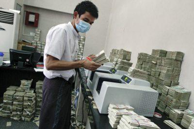 An employee counts Myanmar kyat banknotes in a bank in Yangon (Photo: Reuters/Minzayar).