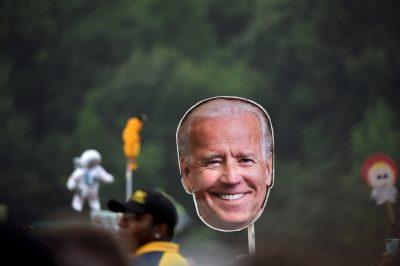 A reveler waves a cardboard cutout of former vice president Joe Biden in Dover, Delaware (Photo: Reuters/Mark Makela).
