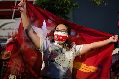 A woman holds a flag as supporters of National League for Democracy gather to celebrate at party headquarters after the general election in Yangon, Myanmar, 9 November 2020 (Photo: Reuters/Shwe Paw Mya Tin).