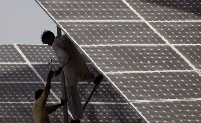 Technicians work on solar panels at a power station in Hub, Pakistan, 19 June 2010 (Photo: Reuters)