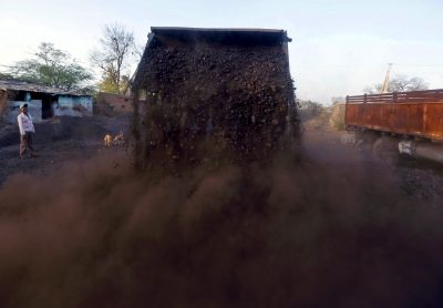 A worker watches as a loader unloads coal at a yard on the outskirts of Ahmedabad, India, 12 February 2016. India is asking the country's big steelmakers to consider converting local medium-quality coal into premium coking coal to slash an annual import bill of more than $4 billion for buying that grade from countries such as Australia (Photo: Reuters/Amit Dave).