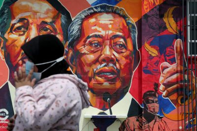 A woman passes by a mural depicting Malaysia's Prime Minister Muhyiddin Yassin in Kuala Lumpur, Malaysia, 27 October 2020. (Photo: Reuters/Lim Huey Teng).