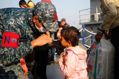 A Bangladesh navy personnel helps a child to wear a mask before getting on board a ship to move to Bhasan Char island, Bangladesh, 29 December 2020 (Photo: Reuters/Mohammad Ponir Hossain).