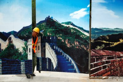 A worker looks through the fence of a construction site that is decorated with pictures of the Great Wall at Badaling, north of Beijing, China, 1 September, 2016 (Photo: Reuters/Thomas Peter).