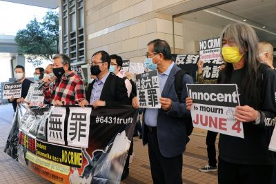 Pro-democracy activists Lee Cheuk-yan and Leung Kwok-hung, also known as 'Long Hair', hold placards outside West Kowloon Magistrates' Courts before facing charges related to an illegal vigil assembly commemorating the 1989 Tiananmen Square crackdown, in Hong Kong, 5 February 2021 (Photo: Reuters/Tyrone Siu).
