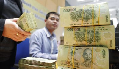 Stacks of 100,000 Vietnamese Dong notes are pictured as employees count money at a branch of the Bank for Investment and Development of Vietnam (BIDV) in Hanoi, 20 January, 2014 (Photo: Reuters/Kham).