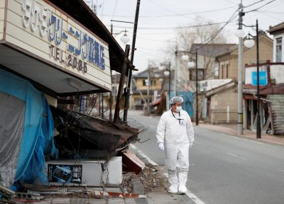 Yuji Onuma, an evacuee from Futaba Town near tsunami-crippled Fukushima Daiichi nuclear power plant, walks next to a collapsed shop on the street in Futaba Town, inside the exclusion zone around the plant, Fukushima Prefecture, Japan, 20 February 2020 (Photo: Reuters/Issei Kato).