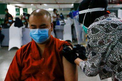 Seorang biksu bereaksi saat menerima vaksin China Sinovac Biotech untuk COVID-19 di tempat parkir Masjid Agung Istiqlal di Jakarta, Indonesia, 25 Februari 2021 (Reuters / Ajeng Dinar Ulfiana).