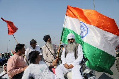 Farmers, of which one holds an India's flag, block an expressway to mark the 100th day of the protest against the farm laws, near Kundli border, in Haryana, India 6 March 2021. (Photo: Reuters/Anushree Fadnavis).