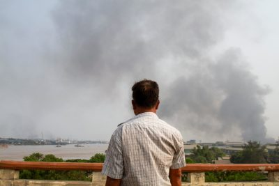 A man looks at smoke believed to be from a factory fire during the security force crackdown on anti-coup protesters at Hlaingthaya, in Yangon, Myanmar, 14 March 2021 (Photo: Reuters/Stringer).